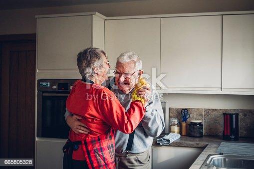 The senior couple dance in their kitchen.