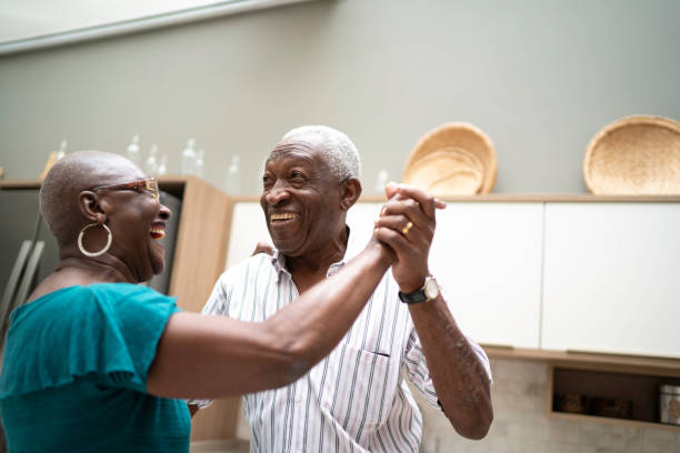 Senior couple dancing at home stock photo