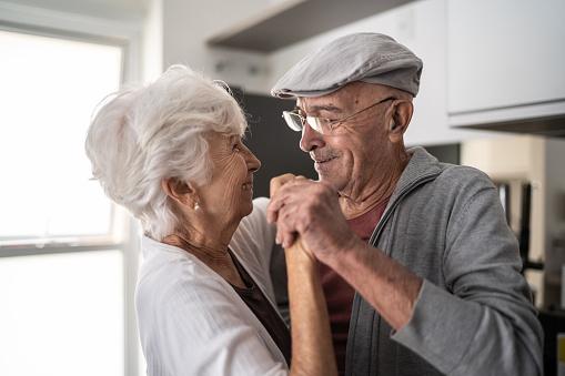 Senior couple dancing at home