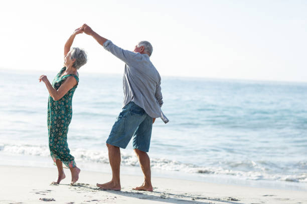 senior couple dancing at the beach - tipo di danza foto e immagini stock