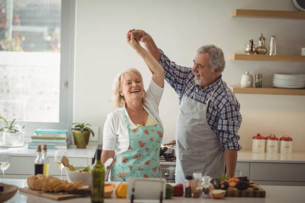 altes paar-tanz in der küche - seniorenwohnungen stock-fotos und bilder