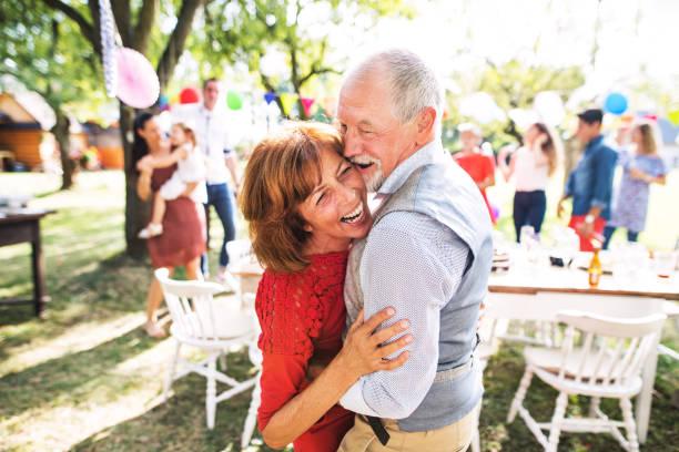 ein älteres paar tanzen auf einer gartenparty draußen im hinterhof. - musik kuchen stock-fotos und bilder