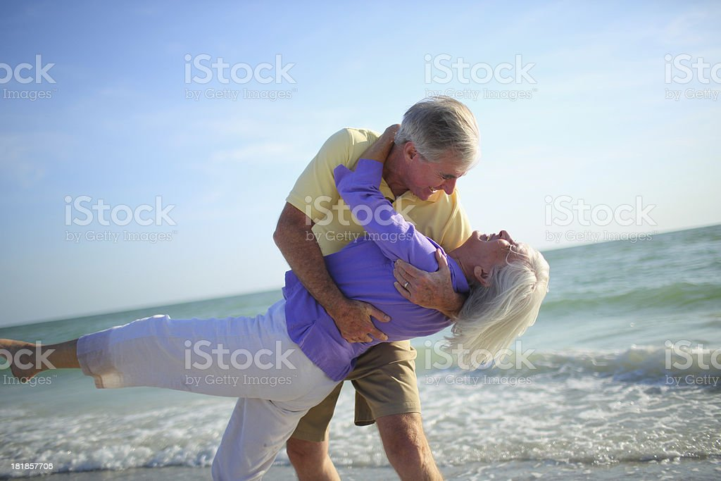 Senior couple dancing on beach royalty-free stock photo