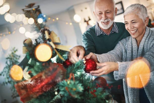 älteres paar einen weihnachtsbaum schmücken. - alte weihnachtsbäume stock-fotos und bilder
