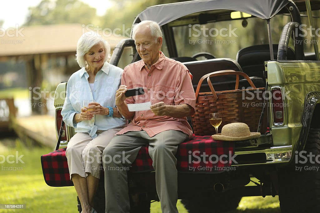 Senior Couple Depositing Check Through Phone In SUV Car stock photo