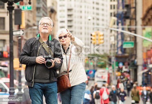 Senior couple discovering New-York City in Autumn. On this photograph, the male is holding a camera and looking up at a building his female partner is pointing to enthusiastically.