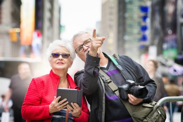pasangan senior menemukan times square di new-york city di musim gugur - traveler new york potret stok, foto, & gambar bebas royalti