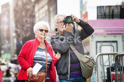 Senior couple discovering Times Square in New-York City in Autumn. On this photograph, the male is holding a camera taking a picture while his female partner is looking next to him with excitement.