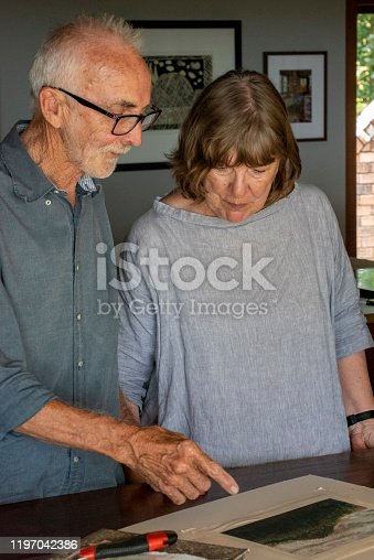 senior couple discuss a pastel drwaing that the man has been working on.