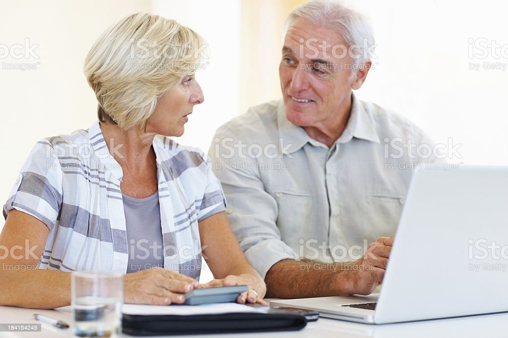 Senior couple calculating their monthly expenses using calculator and...