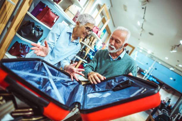älteres paar diskutieren beim betrachten eines roten koffers im ladengeschäft taschen und portemonnaies - trolley kaufen stock-fotos und bilder