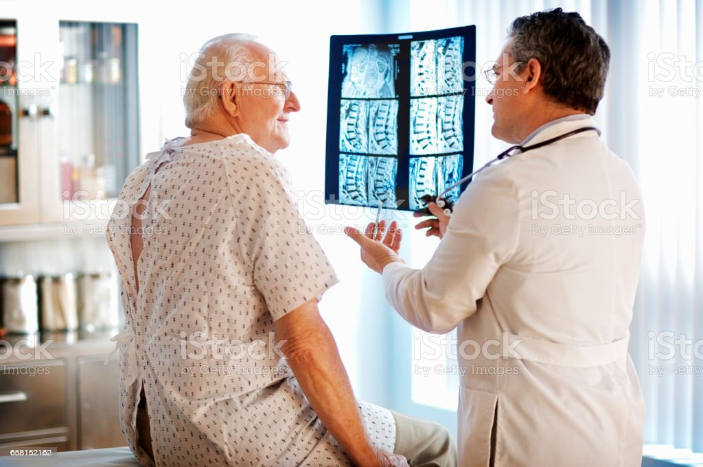 Senior couple discussing X-ray with doctor. stock photo