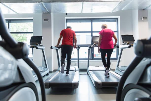 senior couple doing fitness routine at rehab gym - runner rehab gym foto e immagini stock