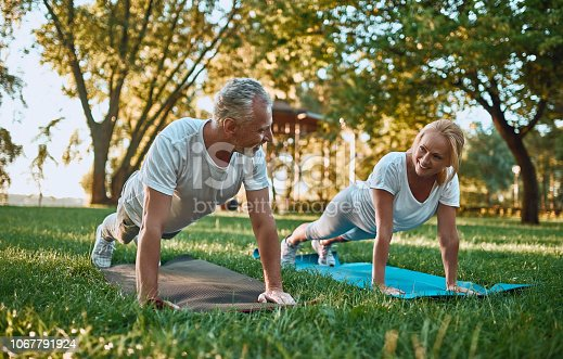 Senior couple is doing sport outdoors. Stretching in park during sunrise. Doing yoga together. Healthy lifestyle concept