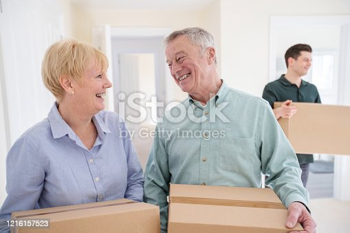 Senior Couple Downsizing In Retirement Carrying Boxes Into New Home On Moving Day With Removal Man Helping