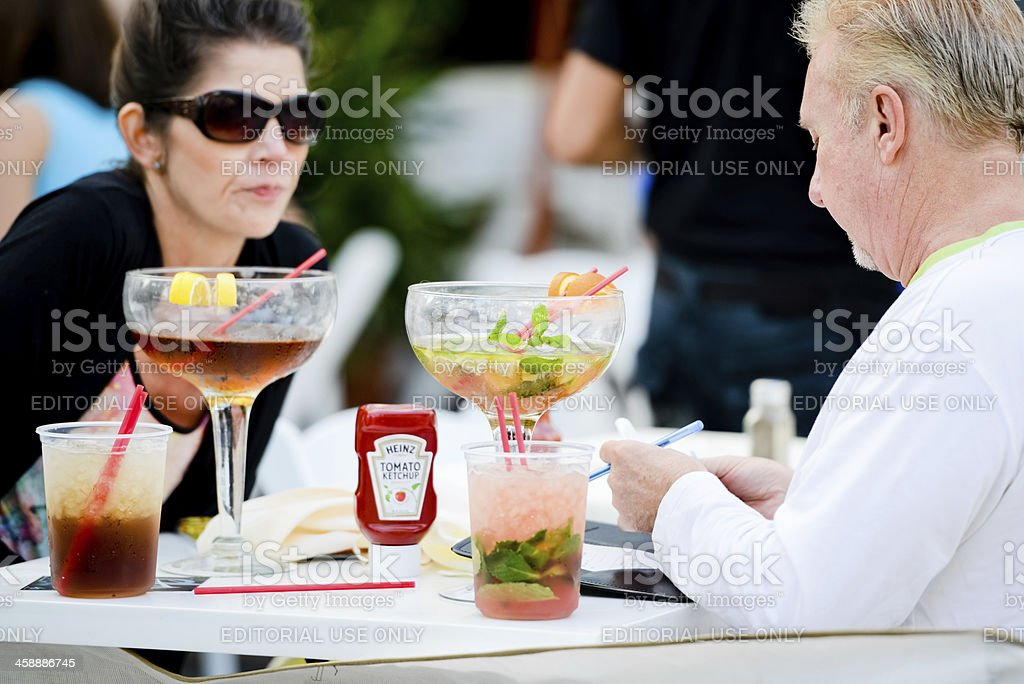 Senior couple drinking cocktails on Ocean Drive, Miami Beach royalty-free stock photo