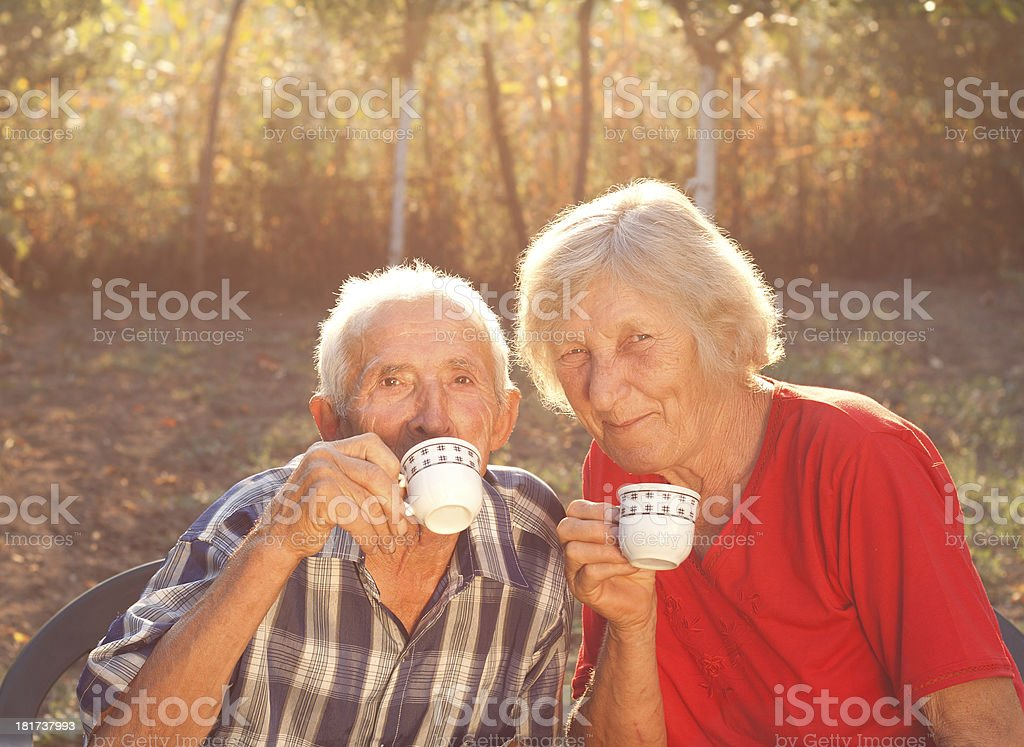 senior couple drinking coffee in the garden royalty-free stock photo