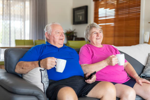 Senior Couple Drinking Cups of Tea or Coffee While Watching TV on the Sofa stock photo