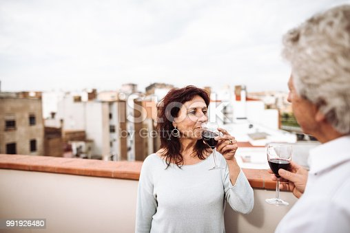 istock senior couple drinking red wine on the terrace 991926480