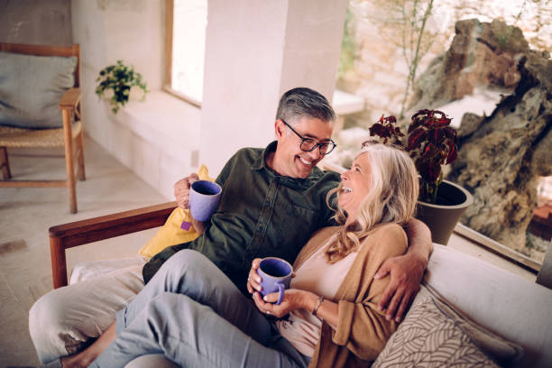 Senior couple drinking tea and laughing together at home stock photo