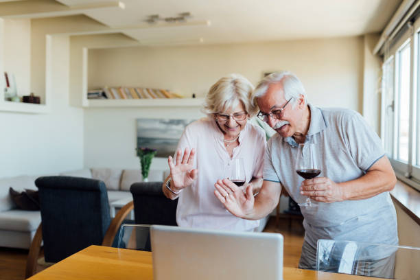 Senior couple drinking wine and chatting with friends and family online stock photo