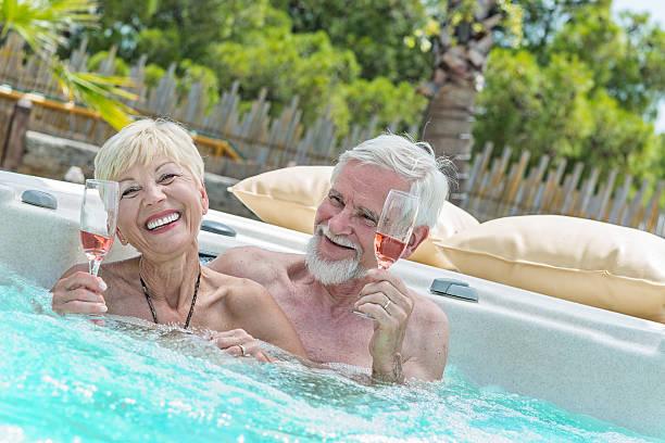 Senior Couple Drinking Wine in hot tub stock photo
