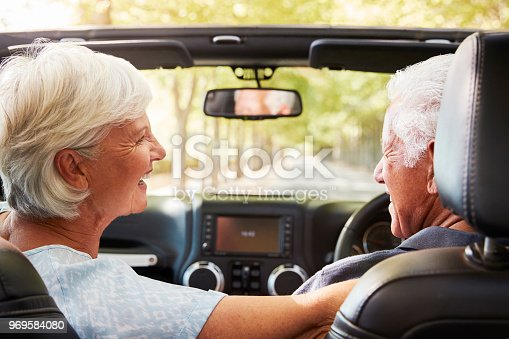 108329737istockphoto Senior Couple Drive Open Top Car On Countryside Road Trip 969584080