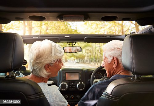 108329737istockphoto Senior Couple Drive Open Top Car On Countryside Road Trip 969584090