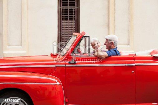 108329737 istock photo Senior couple driving a classic car 186794087