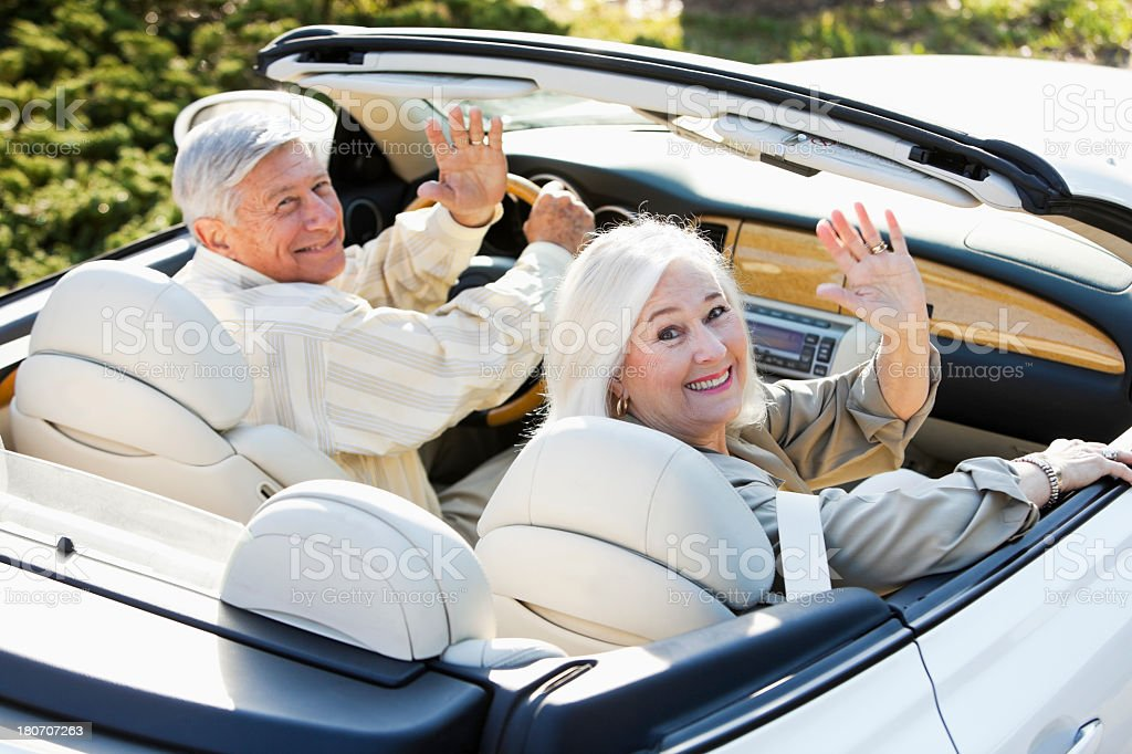 Senior couple driving away in convertible royalty-free stock photo