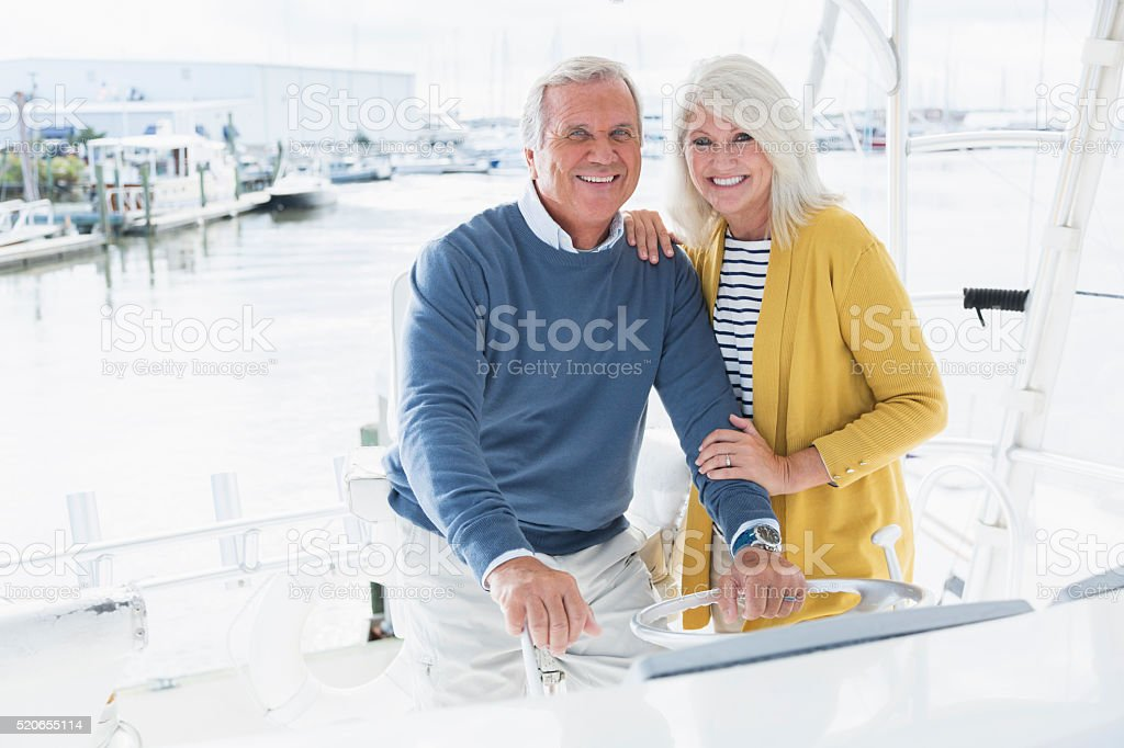 Senior couple driving boat out of marina stock photo