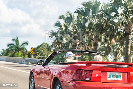 108329737istockphoto Senior couple driving on sports car on road, highway with palm trees in Florida 994759404