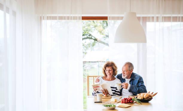 senior paar eten ontbijt thuis. - woman home magazine stockfoto's en -beelden