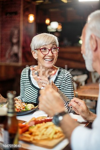 Active senior couple having a lunch in the restaurant. Drinks and food are on the table.