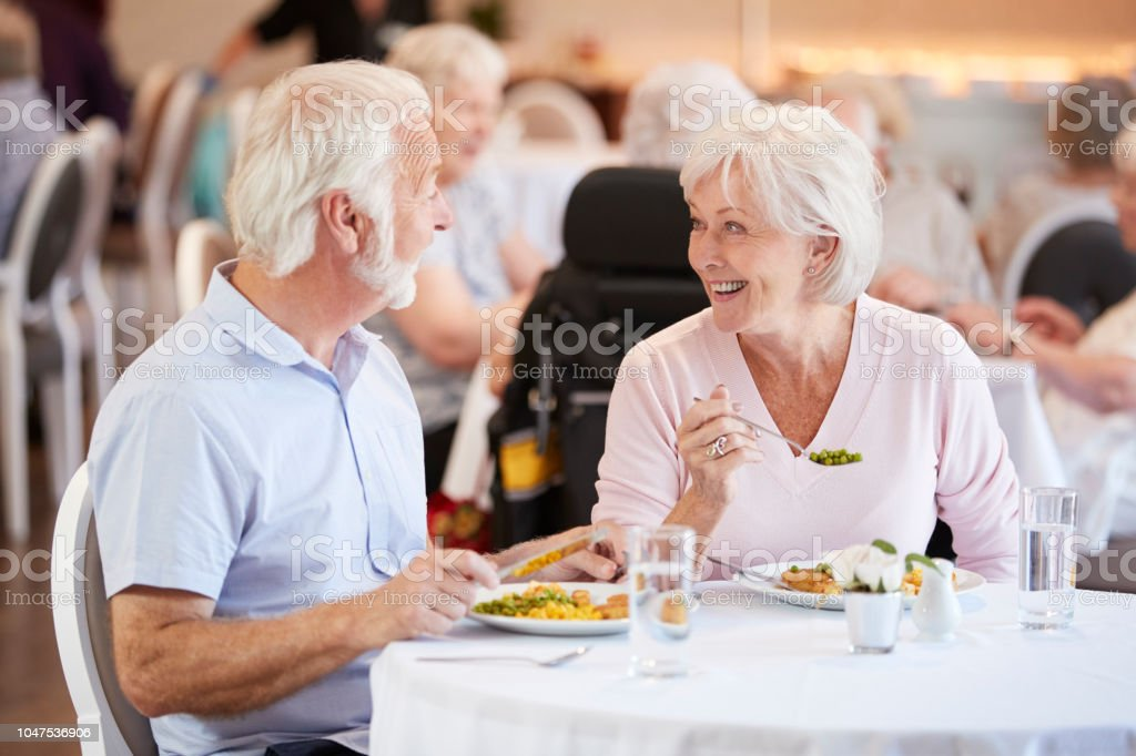 Senior Couple Eating Meal And Talking In Retirement Home stock photo