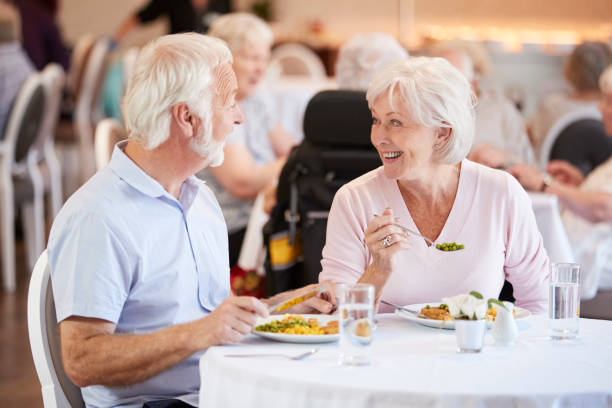 Senior Couple Eating Meal And Talking In Retirement Home Senior Couple Eating Meal And Talking In Retirement Home retirement community stock pictures, royalty-free photos & images
