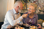 Senior couple in a restaurant, eating sushi. About 65 years old, Caucasian people.