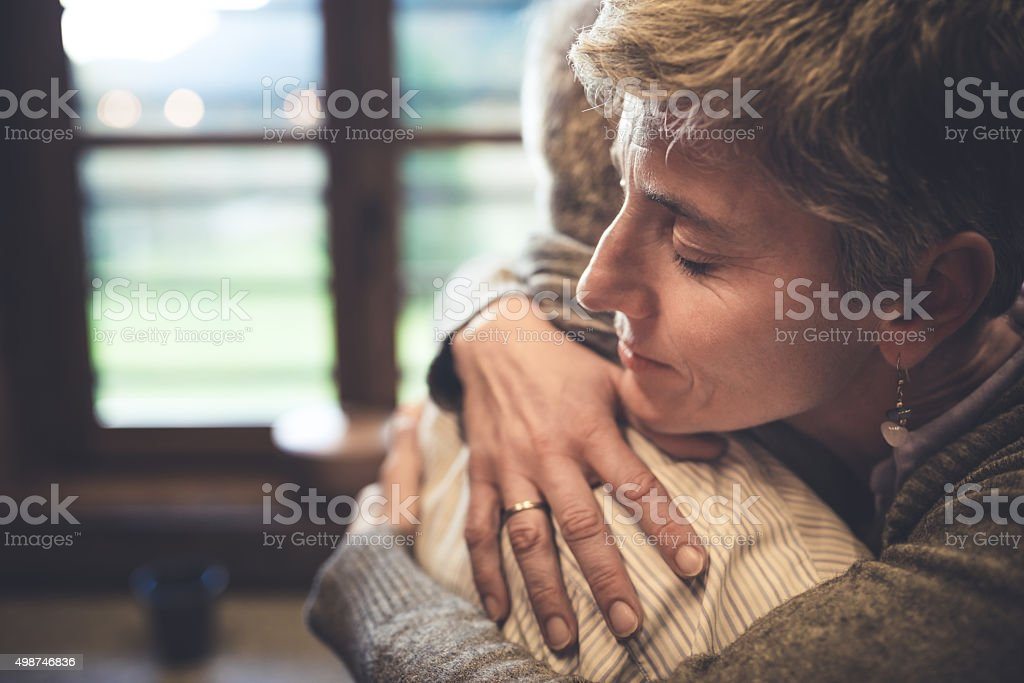 Senior couple embrace in kitchen Senior couple embrace themselves in their kitchen 2015 Stock Photo