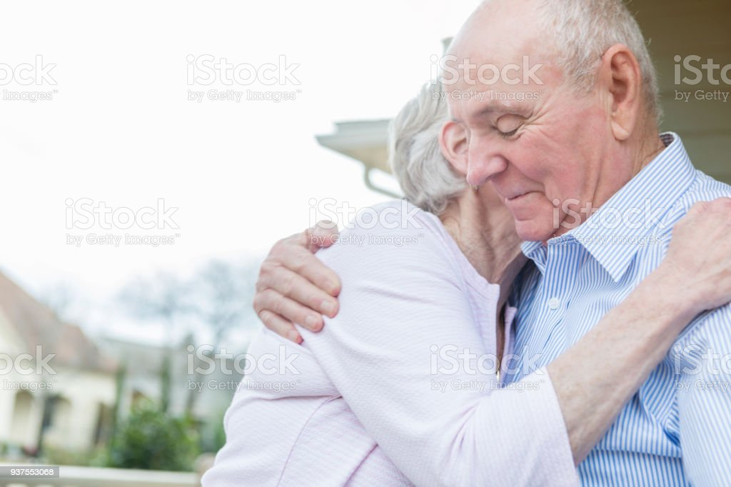 Senior couple embrace on front porch stock photo