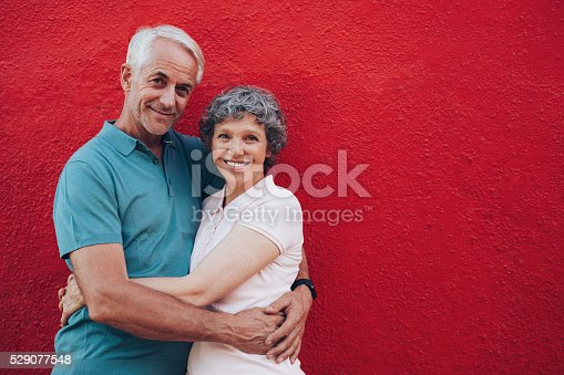 529076288 istock photo Senior couple embracing against red wall 529077548