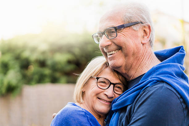 Senior couple embracing each other in backyard A photo of senior couple embracing each other. Happy retired man and woman wearing eyeglasses. They are smiling in backyard. 65 69 years stock pictures, royalty-free photos & images