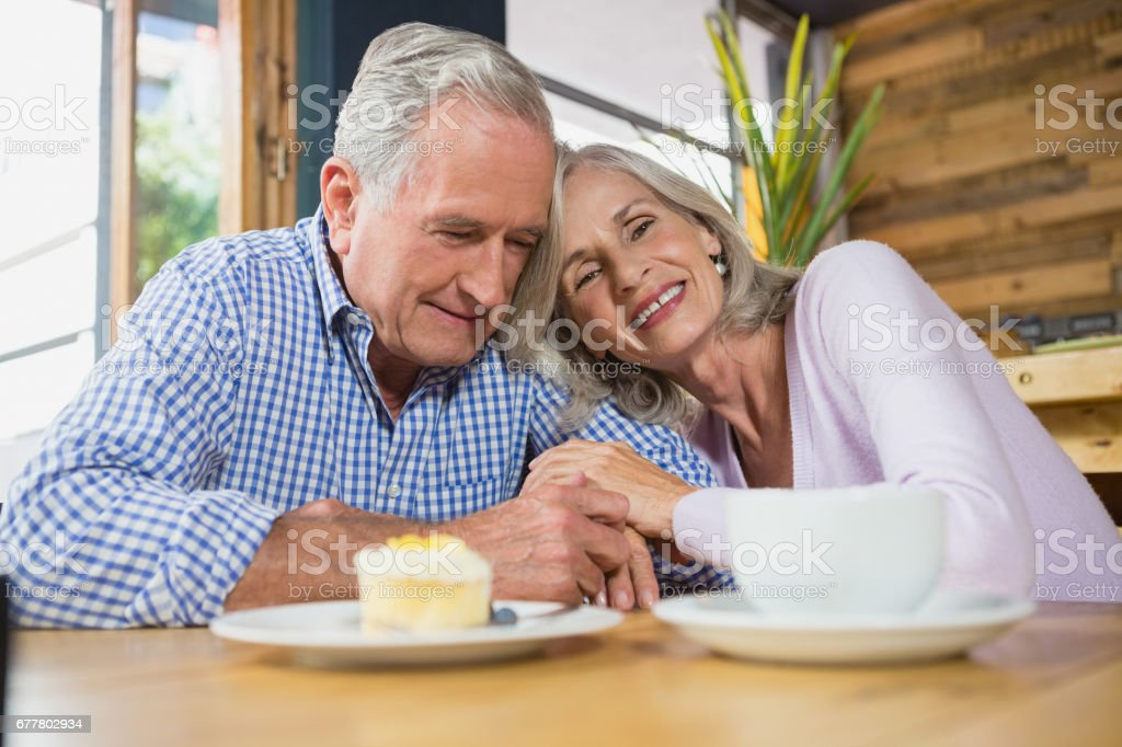 Senior couple embracing each other in café royalty-free stock photo