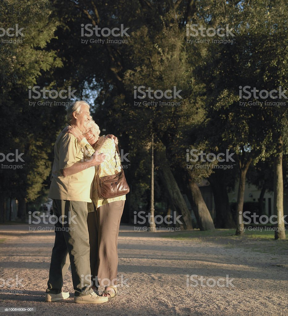 Senior couple embracing in park, smiling foto de stock libre de derechos