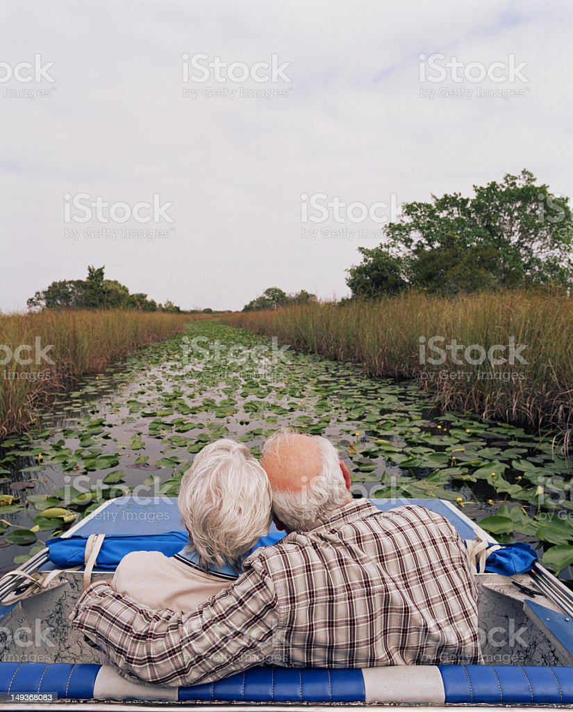 Senior couple embracing on airboat, rear view stock photo