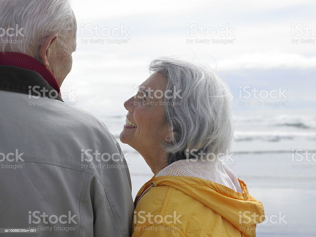 Senior couple embracing on beach, rear view royalty-free stock photo