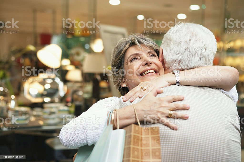Senior couple embracing outside shop, woman smiling, close-up royalty-free stock photo