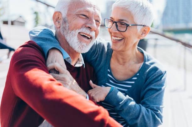 senior paar omarmen - ouder volwassenen koppel stockfoto's en -beelden