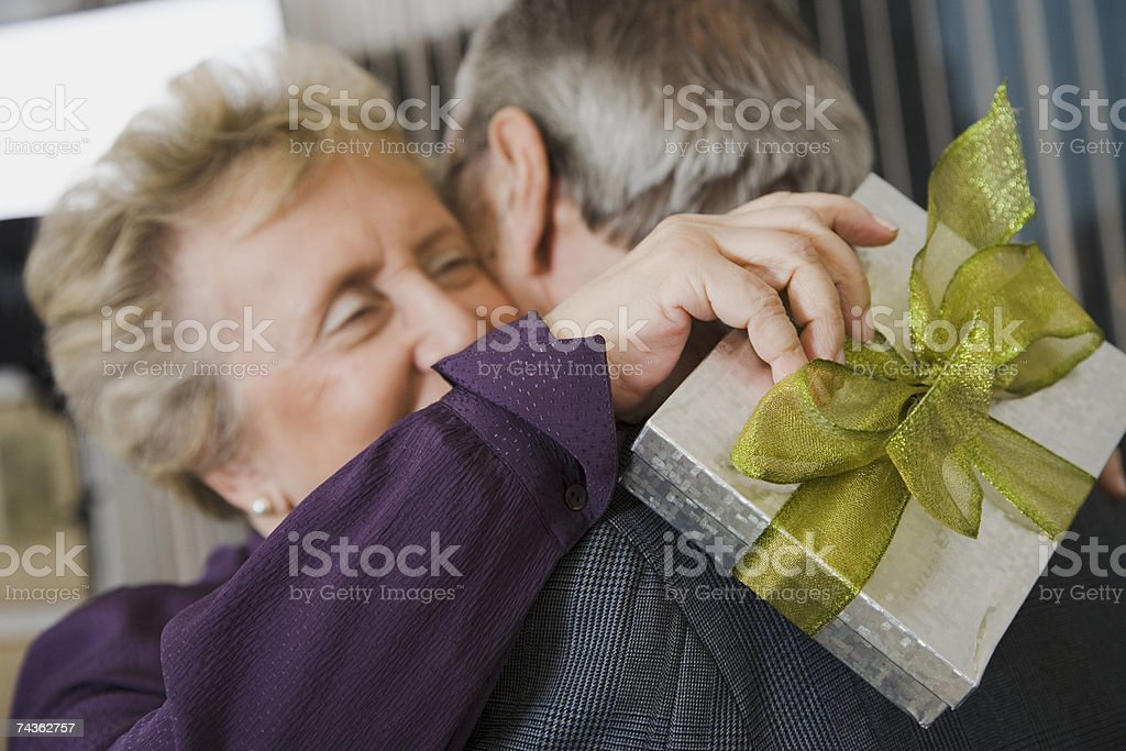 Senior couple embracing, woman holding gift, close-up, differential focus foto de stock royalty-free