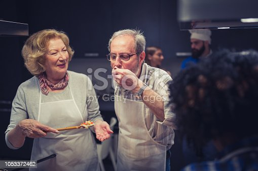 Senior couple, attendees of cooking class preparing meal