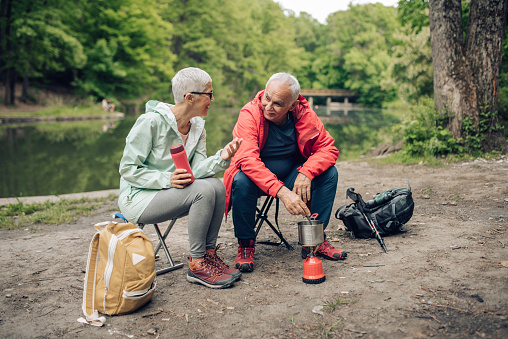 Senior couple preparing tea and enjoying their camping adventure by the river.